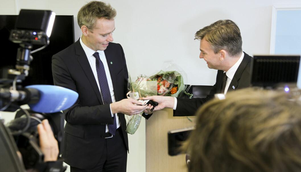 Henrik Asheim (H) overrekker nøkkelkortet til Ola Borten Moe, påtroppende forsknings- og høyere utdanningsminister.